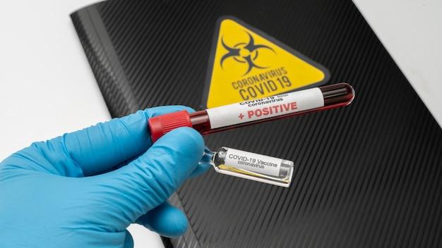 Der arzt hält den covid 19 coronavirus-impfstoff in der hand, eine infizierte blutprobe im probenröhrchen. impfstoff zur vorbeugung, immunisierung und behandlung von covid-19
