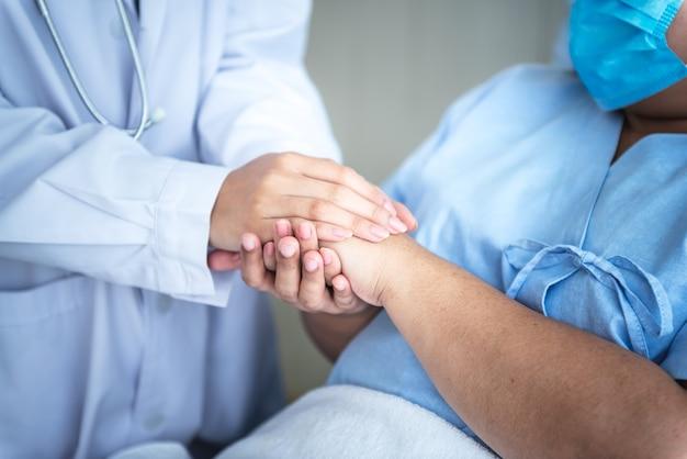 Der arzt hält die hände des patienten, der eine op-maske trägt und im bett des patienten liegt, um zu ermutigen