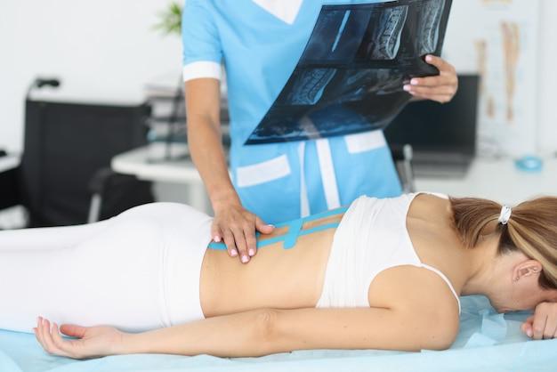 Der arzt hält ein röntgenbild der wirbelsäule in seinen händen und behandelt den patienten.