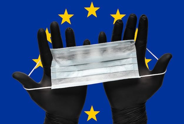 Der arzt hält eine gesichtsmaske in den händen in schwarzen medizinischen handschuhen auf der hintergrundfarbenflagge der eu. pandemieversicherung coronavirus, grippe, luftkrankheiten, grippe. medizinische atemmaske für den menschen.
