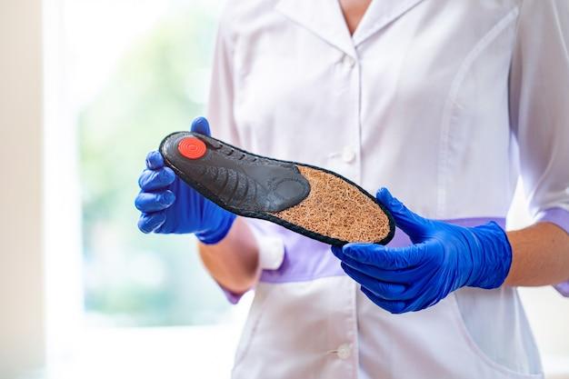 Der arzt hält eine orthopädische innensohle für bequemes tragen von schuhen