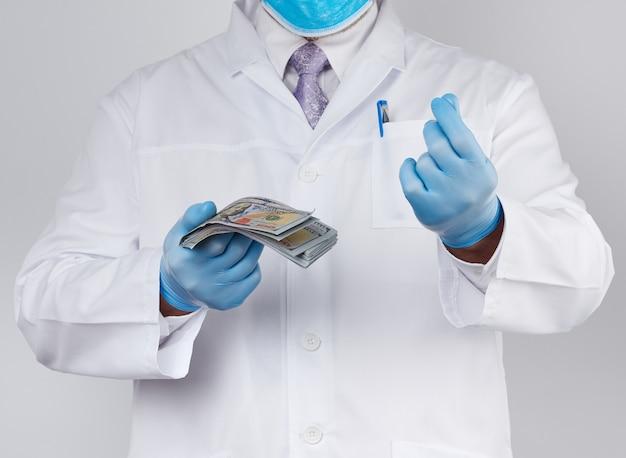 Der arzt hält eine packung papiergeld, antikorruptionskonzept, bestechung und bezahlung in der hand