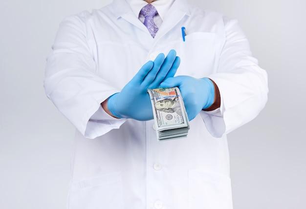 Der arzt hält eine packung papiergeld in der hand und weigert sich, bestechungsgelder anzunehmen