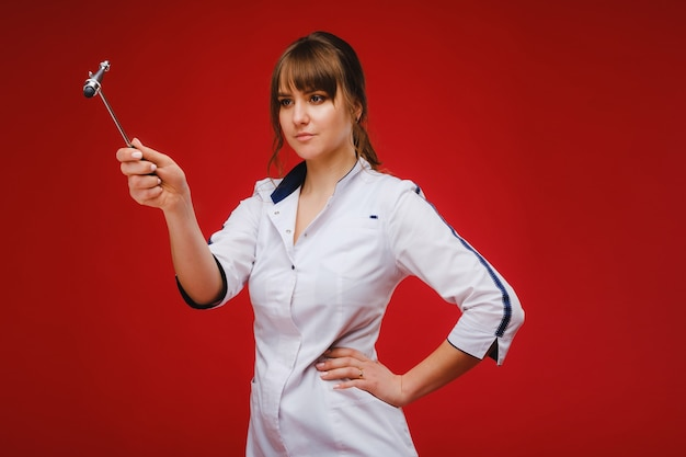 Der arzt hält einen neurologischen hammer auf einen roten