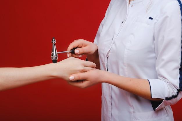 Der arzt hält einen neurologischen hammer auf rotem grund. der neurologe überprüft die reflexe des patienten mit einem hammer. diagnostik, gesundheit und medizinische versorgung