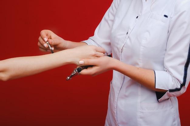 Der arzt hält einen neurologischen hammer auf rotem grund. der neurologe überprüft die reflexe des patienten mit einem hammer. diagnostik, gesundheitswesen und medizinische versorgung.