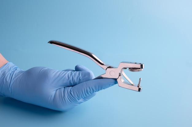Der arzt hält professionelle zahnarztwerkzeuge am blauen tisch