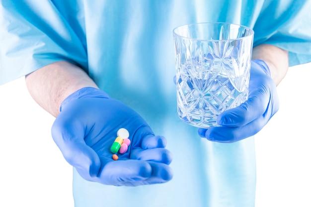Der arzt hält tabletten und ein glas wasser hin. medizinisches konzept.