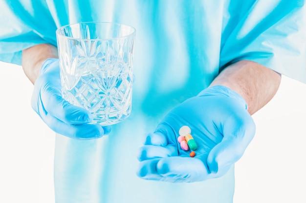 Der arzt hält tabletten und ein glas wasser hin