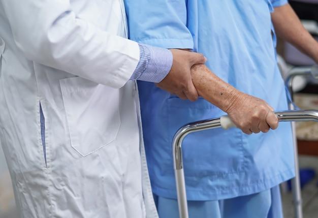 Der arzt hilft asiatischen älteren patienten, mit walker im krankenhaus zu gehen.