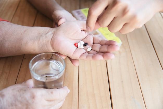 Der arzt hilft dem patienten, die medizintablette in der pillendose richtig zu essen