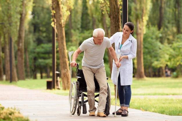 Der arzt hilft einem älteren patienten, auf die beine zu kommen