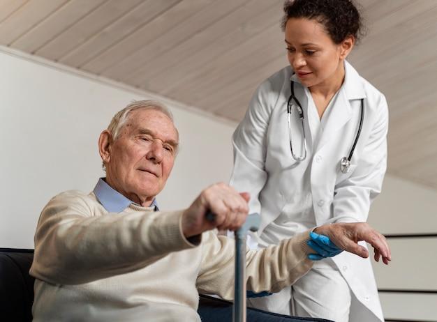 Der arzt hilft ihrer alten patientin aufzustehen