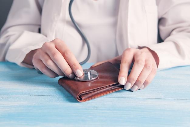 Der arzt hört mit einem stethoskop auf die brieftasche. finanzanalyse