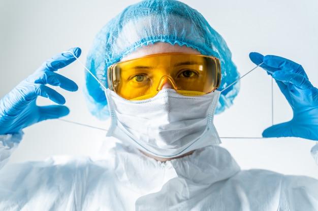 Der arzt im schutzanzug setzt eine maske auf. coronavirus-epidemie im jahr 2020