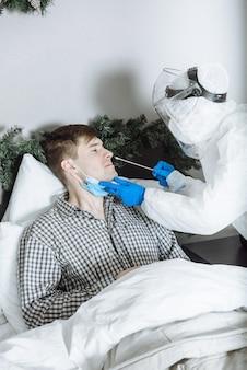 Der arzt in einem psa-schutzanzug führt einen pcr-test auf das coronavirus covid-19 durch.