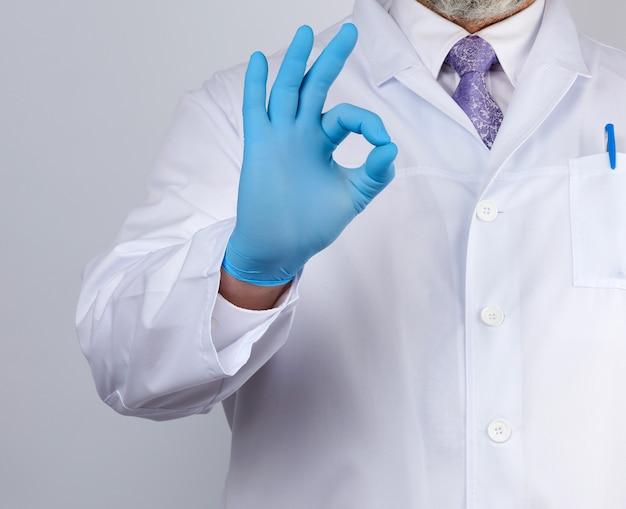 Der arzt in einem weißen kittel mit knöpfen zeigt eine geste in ordnung mit seinen händen und trägt blaue medizinische handschuhe