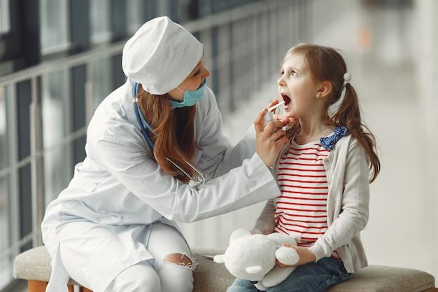 Der arzt in einer maske schont das hals-antiseptikum für ein kind
