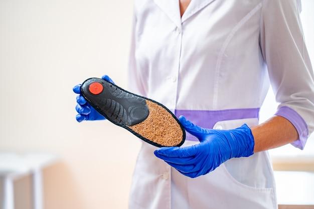 Der arzt in medizinischen gummihandschuhen hält eine orthopädische innensohle