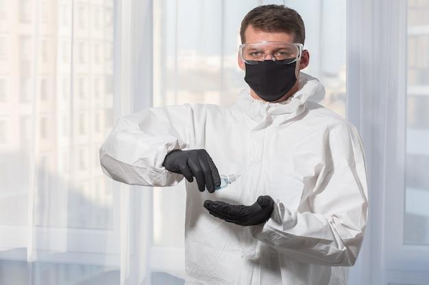 Der arzt in psa-anzuguniform und handschuhen behandelt die hände mit einem antiseptikum. coronavirus-ausbruch. konzept der covid-19-quarantäne. arzt und medizinische versorgung. persönliche schutzausrüstung stoppen sie den virus.