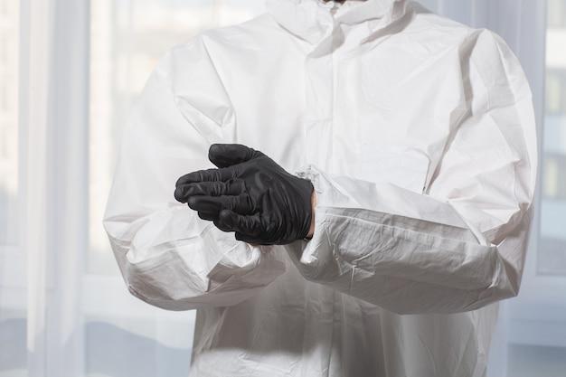 Der arzt in psa-anzuguniform und handschuhen behandelt die hände mit einer antiseptischen nahaufnahme. coronavirus-ausbruch. konzept der covid-19-quarantäne. arzt und medizinische versorgung. persönliche schutzausrüstung stoppen sie den virus.