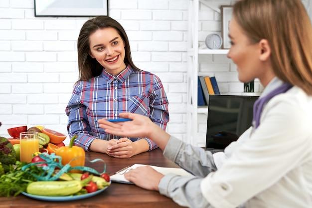 Der arzt in seiner praxis sagt dem mädchen, wie man isst und eine diät einhält