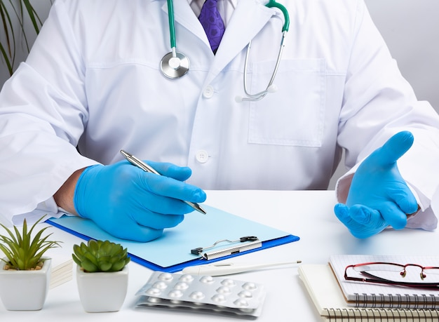 Der arzt in weißer uniform sitzt an einem weißen tisch und schreibt mit sterilen handschuhen an den händen in ein notizbuch
