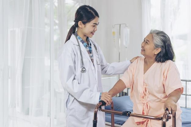 Der arzt ist gut aufgehoben, um ältere patienten im krankenhausbett zu versorgen. patienten fühlen sich glücklich - medizinisches und medizinisches konzept