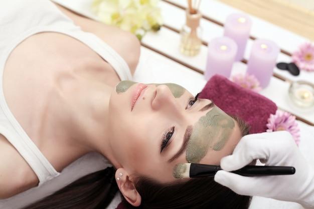 Der arzt ist kosmetikerin für die reinigung und befeuchtung der haut und trägt eine maske mit einem stift auf das gesicht einer jungen frau im schönheitssalon auf. kosmetologie und professionelle hautpflege.