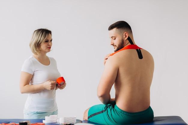 Der arzt klebt ein spezielles behandlungsband auf den ellbogen eines mannes