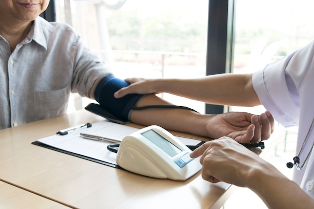 Der arzt maß den druck des patienten mit einem manometer.