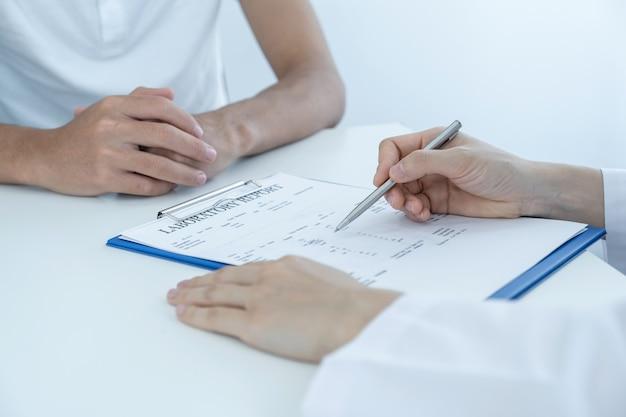Der arzt meldet die ergebnisse der gesundheitsuntersuchung und empfiehlt den patienten medikamente.