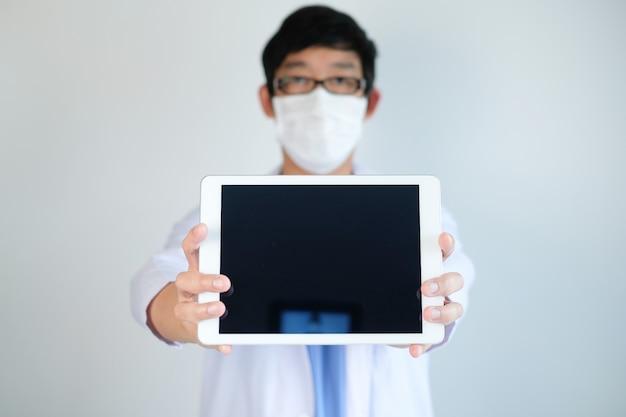 Der arzt nutzt das mobiltelefon und das tablet für das koronavirus, covid19 per telemedizin und ruft nach mornitor, aktualisiert und überprüft den behandlungstest und die gleitlinie während der selbstquarantäne, isolation.