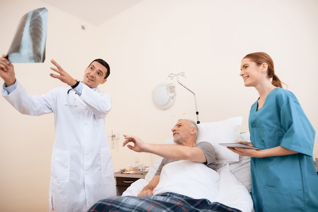 Der arzt schaut auf das röntgenbild des alten mannes