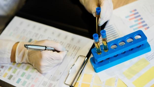 Der arzt schreibt die ergebnisse der analyse in ein formular. auf dem tisch liegen urinröhrchen. krankheitsanalyse und diagnosekonzept.