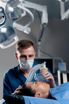 Der arzt setzt auf der intensivstation eine maske zur künstlichen beatmung der lunge auf