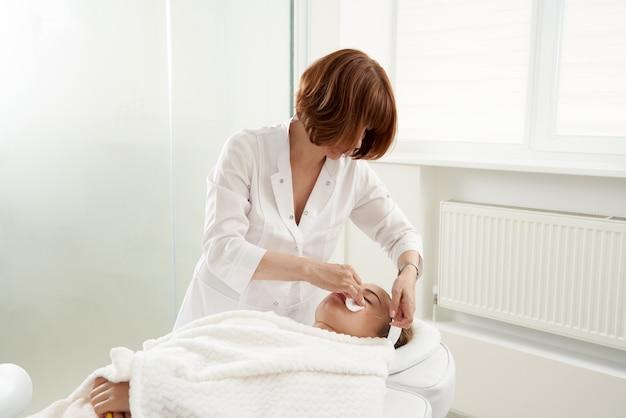 Der arzt setzt nadeln in das weibliche gesicht bei der akupunkturbehandlungstherapie in der spa-salon-alternative