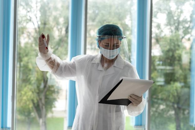 Der arzt sieht sich die ergebnisse des labortests in der zwischenablage an und hält ein reagenzglas in der hand