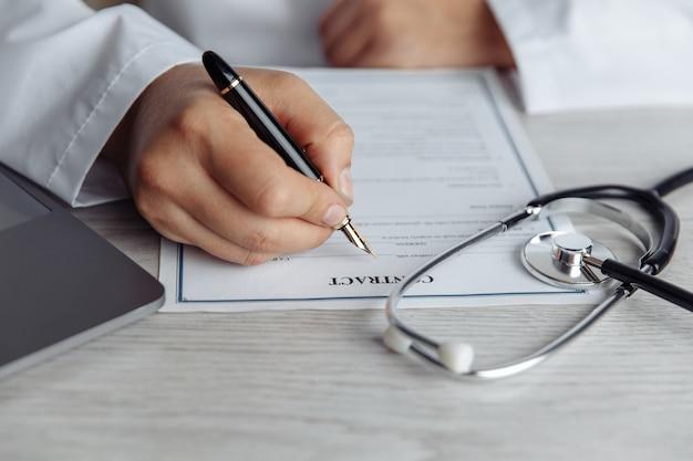 Der arzt sitzt am tisch und unterschreibt das medizinische dokument im büro