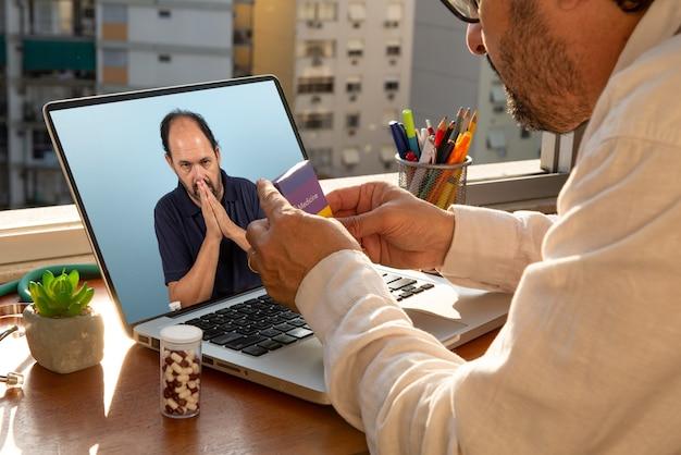Der arzt spricht während der coronavirus-pandemie in seinem büro per telemedizin mit seinem patienten und erklärt, wie das arzneimittel richtig angewendet wird. der patient ist verzweifelt nach covid-19