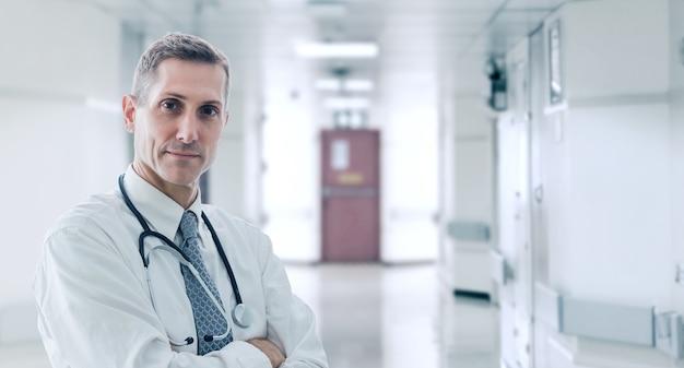 Der arzt steht in selbstbewusster haltung und wartet auf hilfe für seinen patienten in seinem büro, im gesundheitswesen und im medizinischen konzept.