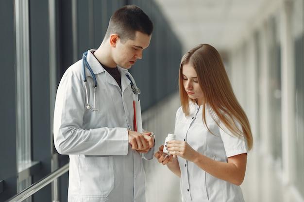 Der arzt teilt tabletten in händen an einen anderen arzt