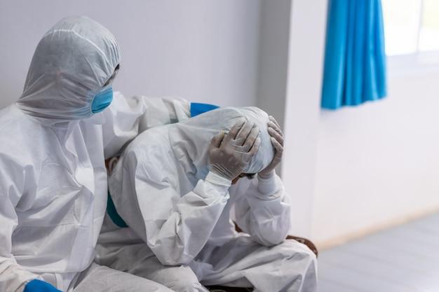 Der arzt tröstet einen kollegen im stress der arbeit in psa-anzuguniform hat stress bei coronavirus-ausbruch oder covid-19