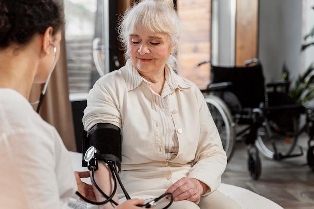 Der arzt überprüft den blutdruck ihrer patientin
