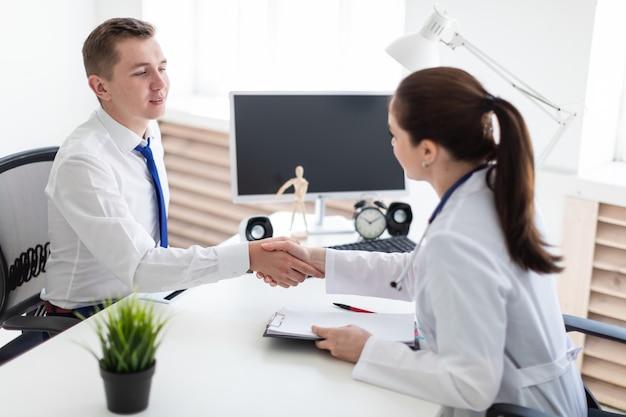 Der arzt und der patient geben sich die hand.