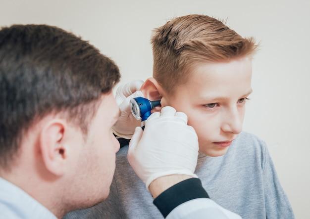 Der arzt untersucht das jungenohr mit einem otoskop. medizinische ausrüstung.