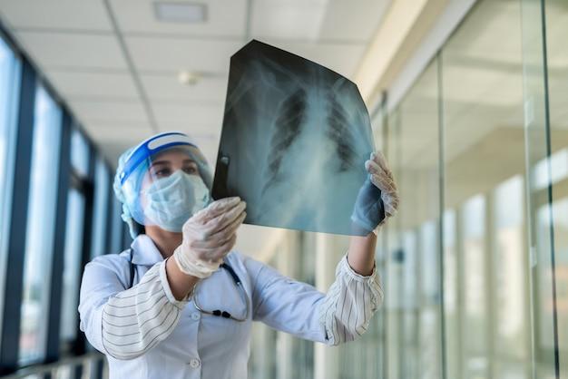 Der arzt untersucht das röntgenbild der lunge im gesichtsschutz und in der maske, um eine lungenentzündung zu bestimmen, die durch ein neues virus covid19 verursacht wird