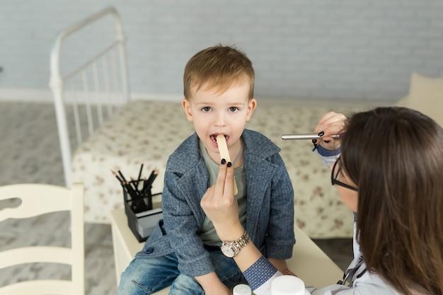Der arzt untersucht den hals des kindes. junge in der kinderarztpraxis.