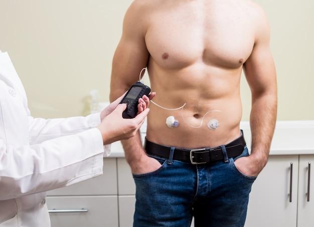 Der arzt verbindet eine insulinpumpe mit einem patienten mit diabetes. konzept von diabetes.