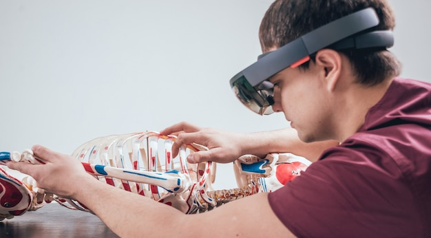 Der arzt verwendet eine augmented-reality-brille, um das menschliche skelett zu untersuchen